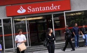 People walk by an agency of the biggest Spanish bank Santander at the