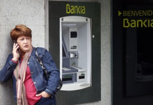 A woman speaks on her mobile phone next to an ATM of Spain's lender bank Bankia in Madrid